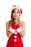Asian Christmas girl with Santa Claus clothes is praying Stock Photo
