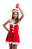 Asian Christmas girl with Santa Claus clothes and red dumbbell. Royalty Free Stock Image