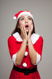 Asian Christmas girl with Santa Claus clothes shock and look up Stock Photos