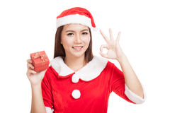 Asian Christmas girl show OK with Santa Claus clothes and red gi Stock Photo