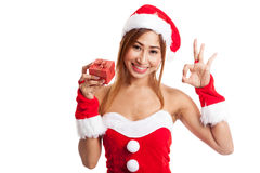 Asian Christmas girl show OK with Santa Claus clothes and red gi Royalty Free Stock Images