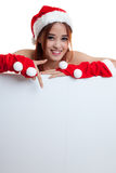 Asian Christmas Santa Claus girl  point down to blank sign. Stock Image