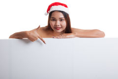 Asian Christmas Santa Claus girl  point down to blank sign. Royalty Free Stock Photo