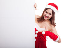 Asian Christmas Santa Claus girl point to blank sign. Royalty Free Stock Images