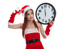 Asian Christmas Santa Claus girl  point to clock at midnight. Stock Image