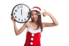 Asian Christmas Santa Claus girl  point to clock at midnight. Royalty Free Stock Photos