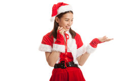 Asian Christmas Santa Claus girl  present space on her hand. Royalty Free Stock Image