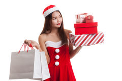 Asian Christmas Santa Claus girl with shopping bags and gift. Royalty Free Stock Photos