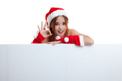 Asian Christmas Santa Claus girl show OK with blank sign. Royalty Free Stock Photo