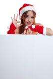 Asian Christmas Santa Claus girl show OK with blank sign. Stock Photos