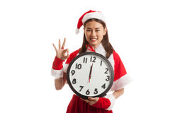 Asian Christmas Santa Claus girl show OK and clock at midnight. Asian Christmas Santa Claus girl show OK  and clock at midnight  isolated on white background Royalty Free Stock Photo