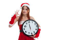 Asian Christmas Santa Claus girl show OK and clock at midnight. Stock Photos
