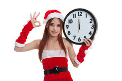 Asian Christmas Santa Claus girl  show OK with clock at midnight. Isolated on white background Royalty Free Stock Images