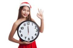 Asian Christmas Santa Claus girl show OK and clock at midnight. Royalty Free Stock Images