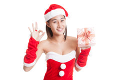 Asian Christmas Santa Claus girl show OK  and  gift box  isolate. D on white background Royalty Free Stock Photo