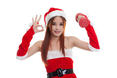 Asian Christmas Santa Claus girl show Ok with red dumbbell. Royalty Free Stock Photo