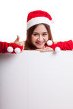 Asian Christmas Santa Claus girl thumbs up with blank sign. Asian Christmas Santa Claus girl thumbs up with blank sign  isolated on white background Stock Photo