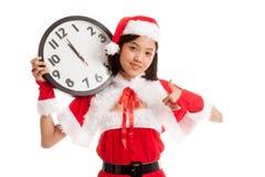 Asian Christmas Santa Claus girl thumbs up with clock at midnig stock photo