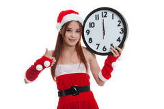 Asian Christmas Santa Claus girl  thumbs up with clock at midnig Royalty Free Stock Images