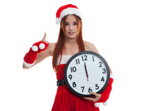 Asian Christmas Santa Claus girl  thumbs up and clock at midnigh Stock Photos
