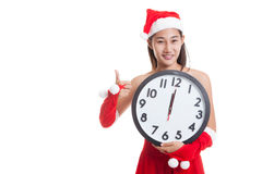 Asian Christmas Santa Claus girl  thumbs up and clock at midnigh. T  isolated on white background Stock Photos