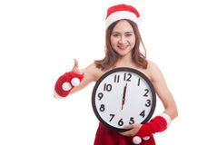 Asian Christmas Santa Claus girl  thumbs up and clock at midnigh Stock Images
