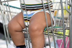 Asian chubby child sits in shopping trolley i Royalty Free Stock Image