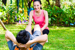 Asian coach helping man with stretching exercises Stock Photos