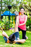 Asian coach helping man with stretching exercises Royalty Free Stock Image