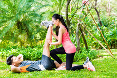 Asian coach helping woman with stretching exercises Royalty Free Stock Photos