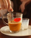 Asian cofe with milk served on table close up photo. With human hands stirring Royalty Free Stock Photos