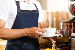 Asian Coffeeshop - barista presents coffee stock images