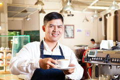 Asian Coffeeshop - barista presents coffee Royalty Free Stock Image