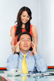 Asian Colleagues having office affair. Business women or secretary giving a massage and having an office affair or relationship with her boss or colleague in stock image
