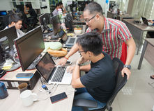 Asian Colleagues Software Developers Team Sitting At Desk. Working Laptop Computer Business People Group Real Office Stock Photo
