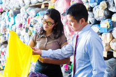 Asian colleagues in a warehouse choosing cloths Stock Photos