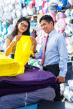 Asian colleagues in a warehouse choosing cloths Royalty Free Stock Image