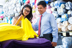Asian colleagues in a warehouse choosing cloths. Indonesian textile workers choosing some colorful fabrics in a asian storehouse Royalty Free Stock Photography