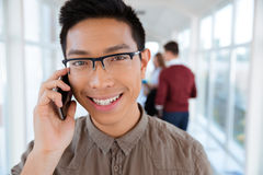 Asian college boy talking on the phone. Portrait of a smiling asian college boy talking on the phone in university hall Royalty Free Stock Images