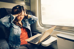 Asian college girl frustrated with laptop on the train, warm light tone, with copy space Royalty Free Stock Photography