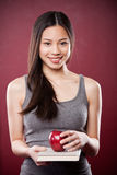Asian college student. A shot of a beautiful asian college student carrying a book and an apple stock image