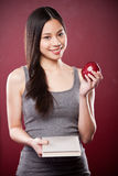 Asian college student. A shot of a beautiful asian college student carrying a book and an apple royalty free stock image
