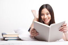 Asian college student. A shot of a beautiful asian college student reading on her bed stock image