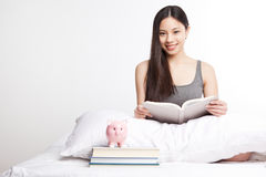 Asian college student. A shot of a beautiful asian college student reading on her bed royalty free stock photos