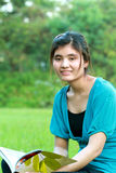 Asian college student. Have a book in hand, look the camera Stock Images