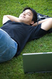 Asian college student. An asian college student lying down on the grass Royalty Free Stock Images