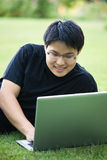 Asian college student. An asian college student working on his laptop outdoor royalty free stock photos