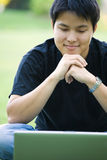 Asian college student. An asian college student working on his laptop outdoor royalty free stock images