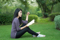Asian college student on campus in park. Asian woman college student on campus. She reading book in park Royalty Free Stock Image