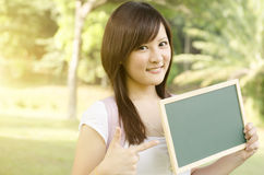 Asian college student pointing at blank chalkboard Stock Images